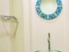 トイレ手洗いスペース。旅先で買った土産物の鏡をアクセントに。