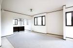 何もない一部屋だった2階にキッチンを設けてLDKに。既存の窓枠に合わせたダークブラウンのラインが効いている。デザイン性を持たせた柱を入れて耐震性も補強。