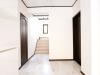 大理石の床が高級感あふれる広い玄関。左側の壁とドアは新設したもの。既存の右側と差が出ないよう細かく配慮した。