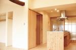 回遊式の造作キッチン。ステンレスの天板にベースから家具調の框扉まで、北海道産唐松の無垢材を使用している。