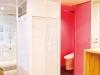"""白のインテリアに鮮やかなピンクのトイレは裏テーマの""""バランス""""にちなむ。"""