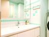 ブルーの珪藻土に2色のタイルをデザイン貼り。既存の洗面台を活かして予算配分しながら、爽やかなサニタリースペースを演出。