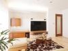 広々とした明るいLDK。テレビは場所をとらない壁掛けにし、空気をきれいにする壁材エコカラットで装飾。造作AVボード下部には照明を仕込み空間に奥行き感を演出。機能とデザインを両立させた。