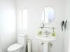 隣接する賃貸アパートを戸建の母家と合体させ、外観はそのままに丸ごとリフォーム。広々としたこだわりのサニタリーは、洗面器はスタンディングタイプのものを選定。床をモザイクタイル貼りにし、壁は白の角タイルで清潔感を出した。