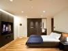 ゆったりとした寝室。ベッド正面に壁面TV収納を配置し、横たわりながら映画鑑賞もできる。ベッド側面には、扉1面が姿見のワードローブ。