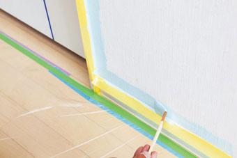 2.隅を塗る(1回目)ペンキは缶をよく攪拌させてからバケットセットに流し入れる。ハケを使用し、養生テープからはみ出さないよう丁寧に塗る。