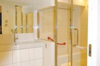 事例4 サニタリーから浴室まで床タイルを一続きにし、ガラスで仕切ることで空間に広がりを持たせた。洗面台は壁付けにして下部に照明を。奥行きを感じる清潔感のある空間が完成。