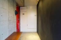 事例1:ベンチ付きのエントランス。印象的な朱赤の玄関扉は奥様選定。向かいの壁には黒板塗料を塗装し、家族や来客のコミュニケーションを図るスペースとしても機能を持たせた。正面の扉はトイレにつながり、回遊性のある間取りとなっている。