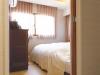 寝室。夫婦ふたりには十分な広さで、大きめのウォークインクローゼットを設けた。照明の操作は、枕元でもできるよう利便性に配慮。