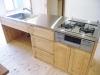 回遊式キッチン。キッチンバック壁一面に、国産杉の吊戸棚とワークカウンターを造作。