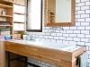 洗面室には、5人家族が朝の支度もスムーズにできるよう、大きな洗面台を設けた。こだわりのタイルの壁が印象的。
