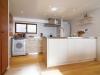 アイランド型オープンキッチン。浴室を広くとるために、洗濯機をキッチンにビルトインした。