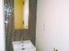 トイレの手洗い器壁はご主人セレクトの輸入ガラスタイルとクリアガラスのブラケット照明をコーディネート。シャープな印象に。